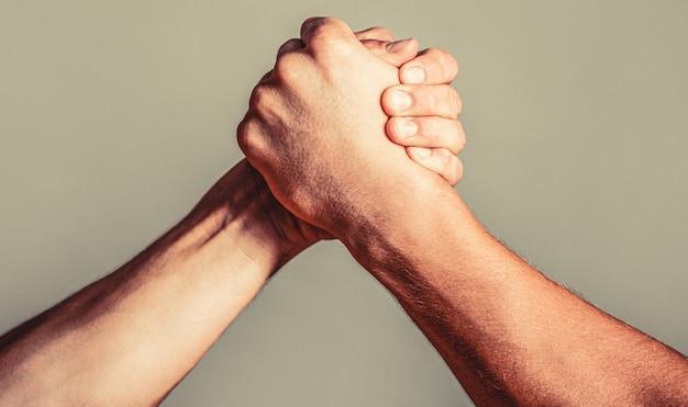 Mão de homem. wrestling de braço de dois homens. luta de braços. close up. aperto de mão amigável, amigos cumprimentando, trabalho em equipe, amizade. aperto de mão, braços, amizade. mão, rivalidade, vs, desafio, comparação de força