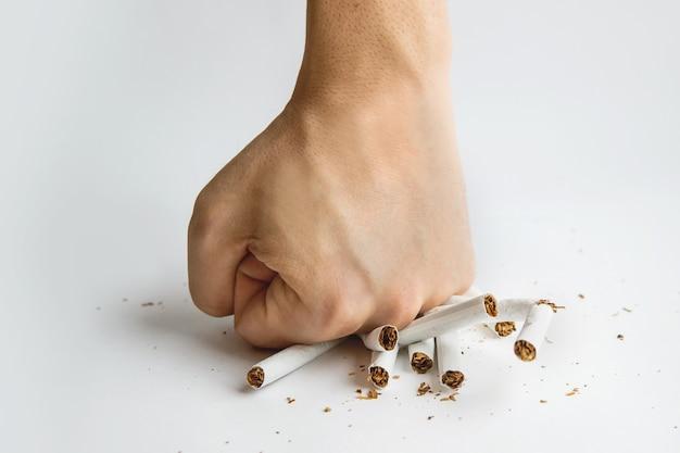 Mão de homens esmagou alguns cigarros, não fumar, parar de fumar e estilo de vida saudável. cara quebra um cigarro com os dedos em fundo branco. os malefícios do tabagismo. parar de fumar.