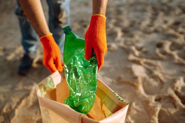 Mão de homens recolhe garrafa de plástico na praia do mar. o voluntário que usa luvas de proteção coleta o plástico da garrafa.