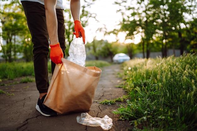 Mão de homens recolhe lixo plástico para limpeza no parque. o voluntário que usa luvas de proteção coleta o plástico da garrafa.