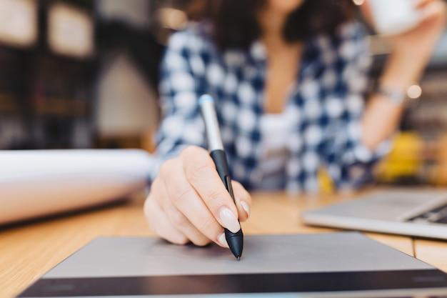 Mão de imagem closeup de mulher projetando na mesa na biblioteca cercam coisas de trabalho. laptop, trabalho criativo, design gráfico, freelancer, estudante inteligente, trabalho de amor.