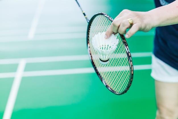 Mão de jogador feminino de badminton segurar o galo de transporte branco com raquete