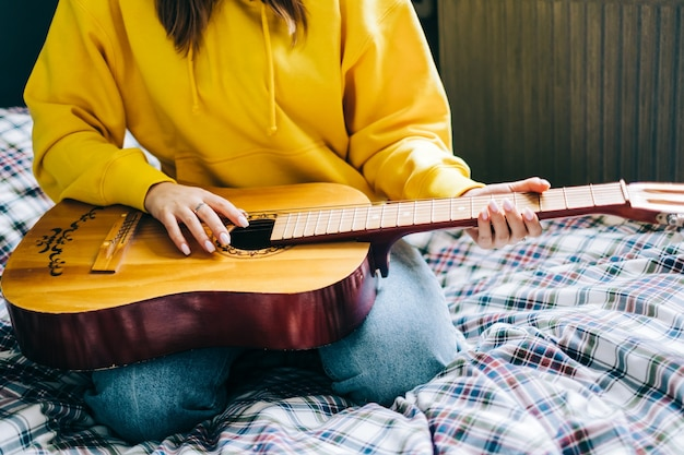Mão de jovem closeup tocando violão em casa.