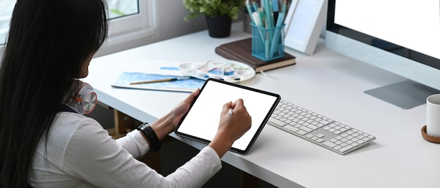 Mão de jovem designer gráfico desenhando no tablet do computador em seu espaço de trabalho criativo