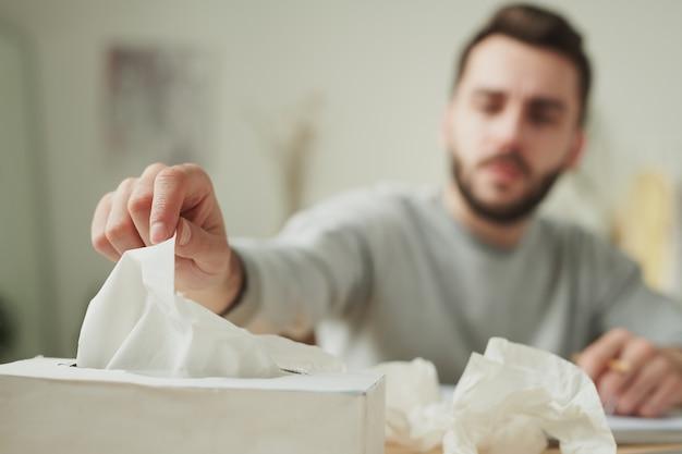Mão de jovem empresário doente tirando lenço de papel da caixa enquanto está sentado à mesa em ambiente doméstico e fazendo plano de trabalho