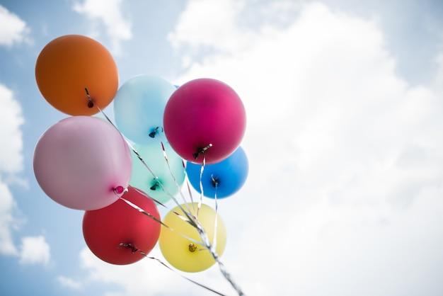 Mão de jovem garota segurando balões coloridos
