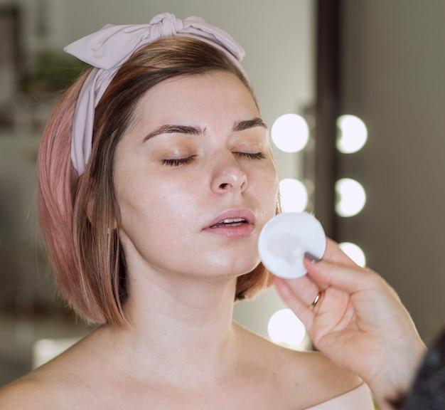 Mão de limpeza de rosto de mulher adorável