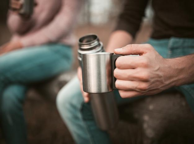 Mão de machos com copo e garrafa térmica, pausa para acampar