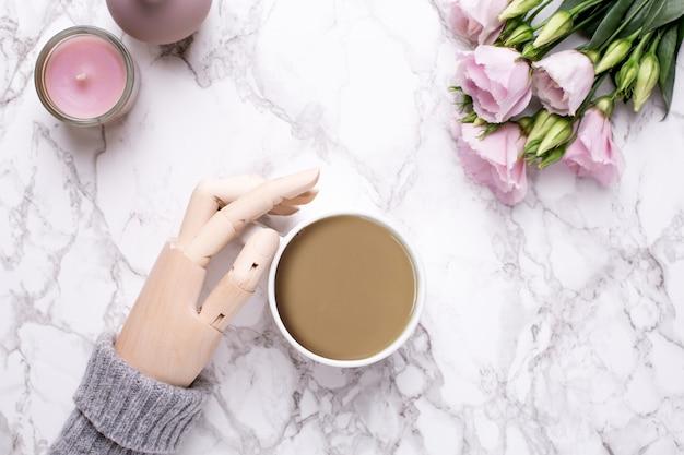 Mão de madeira, café e flores cor de rosa em mármore