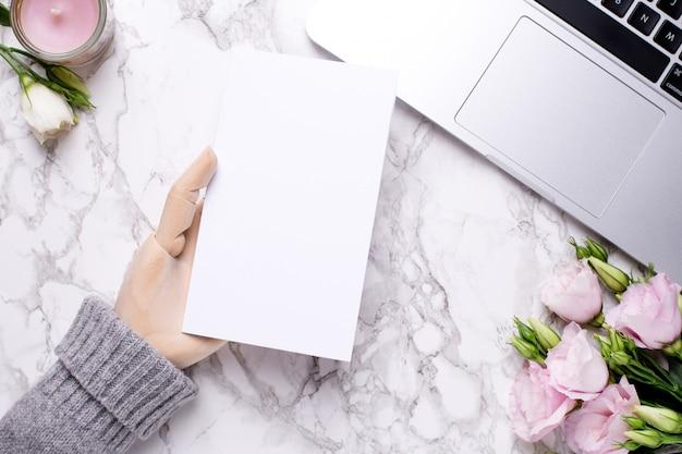 Mão de madeira com cartão presente branco na mesa de escritório de mármore com flores cor de rosa