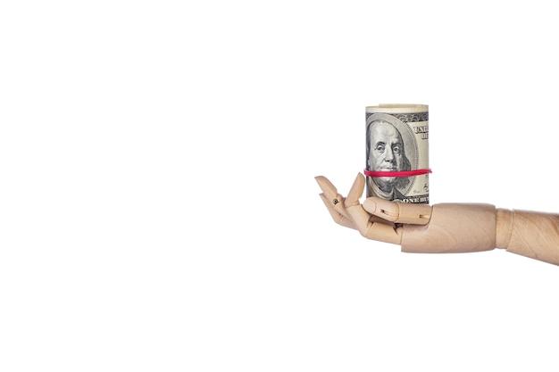 Mão de madeira com dinheiro isolado no fundo branco. rolo de notas de cem dólares. notas de 100 usd, moeda de dólares americanos com espaço de cópia. conceito financeiro mínimo