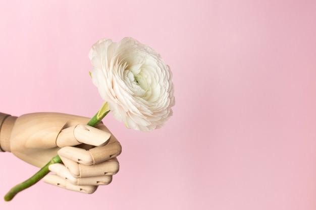 Mão de madeira com uma flor branca em uma rosa
