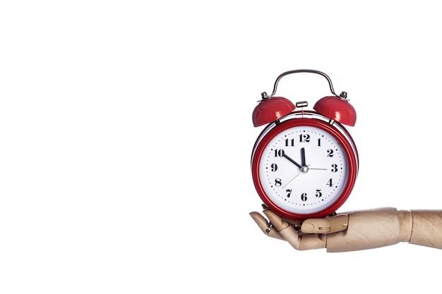 Mão de madeira que mantém o despertador vermelho retro isolado no fundo branco.
