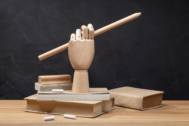 Mão de madeira segurando um lápis em livros. fundo de quadro de giz volta ao conceito de escola.