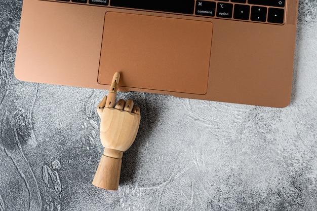 Mão de madeira trabalhando em um laptop. conceito de comunicação e trabalho no escritório.