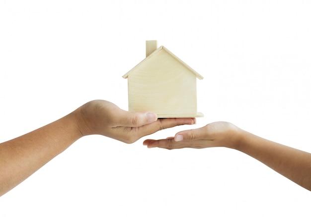 Mão de mãe dando o modelo da casa de madeira para a metáfora da filha o legado do conceito imobiliário