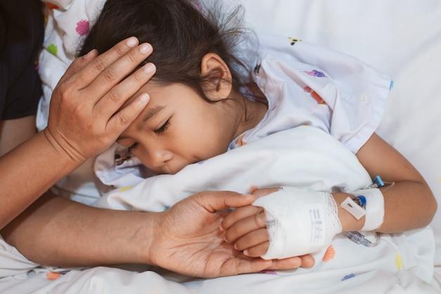Mão de mãe segurando a mão da filha doente que têm solução iv enfaixada