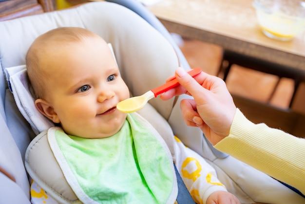 Mão de mães não identificadas alimenta cuidadosamente uma linda garota recém-nascida saudável com comida para bebê.