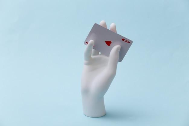 Mão de manequim branco com ás de copas fica sobre fundo azul. poker, jogo de cartas