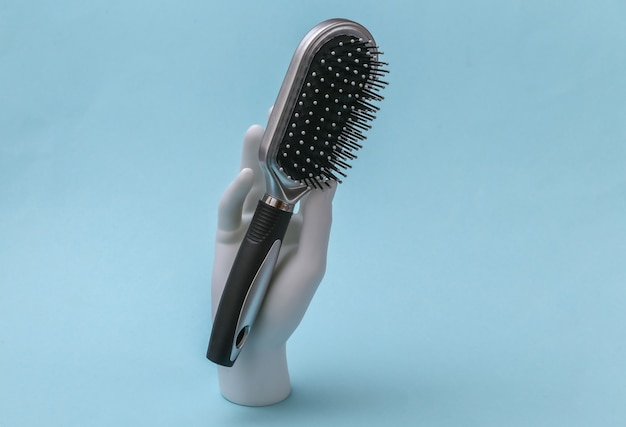 Mão de manequim branco com escova de cabelo fica sobre fundo azul. cuidado do cabelo, conceito de beleza