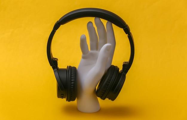 Mão de manequim branco com fones de ouvido fica em fundo amarelo.