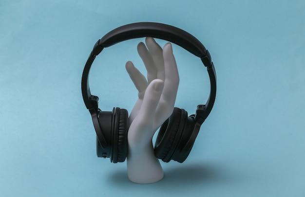 Mão de manequim branco com fones de ouvido fica sobre fundo azul.