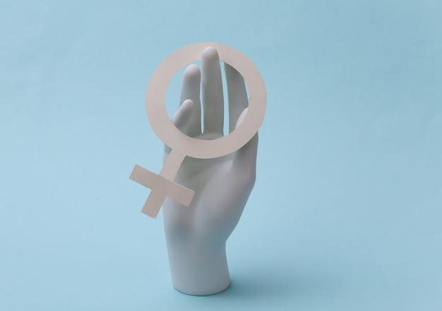 Mão de manequim branco com símbolo do gênero feminino fica sobre fundo azul. feminismo