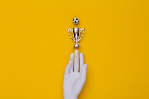 Mão de manequim branco, copa do campeonato e bola sosser sobre um fundo azul. vista do topo Foto Premium