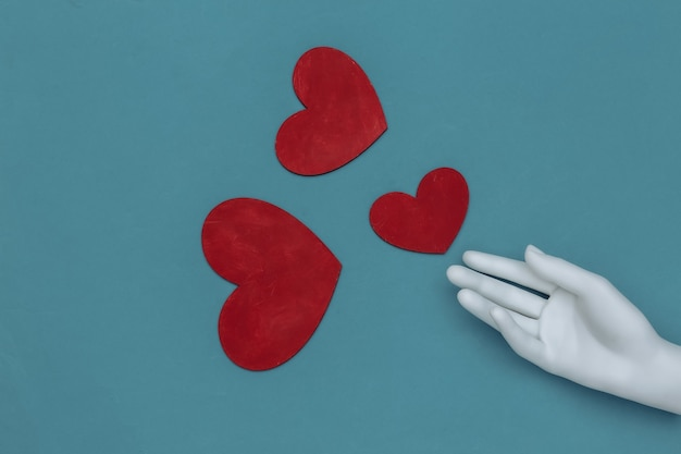 Mão de manequim branco e corações vermelhos sobre fundo azul. vista do topo