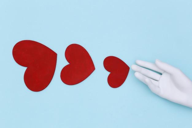 Mão de manequim branco e corações vermelhos sobre um fundo azul. vista do topo