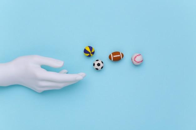 Mão de manequim branco e mini bolas de diferentes esportes em um fundo azul. vista do topo