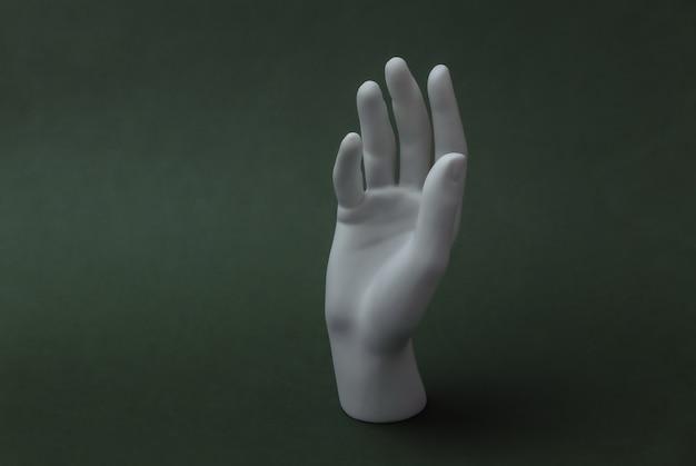 Mão de manequim branco fica sobre fundo verde. minimalismo