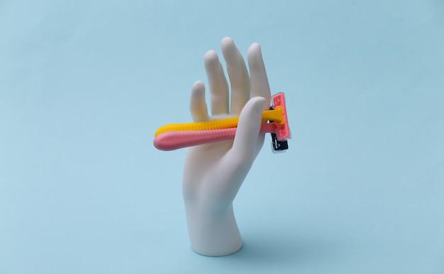Mão de manequim branco segura depiladores de lâmina em fundo azul. beleza, conceito de cuidados pessoais