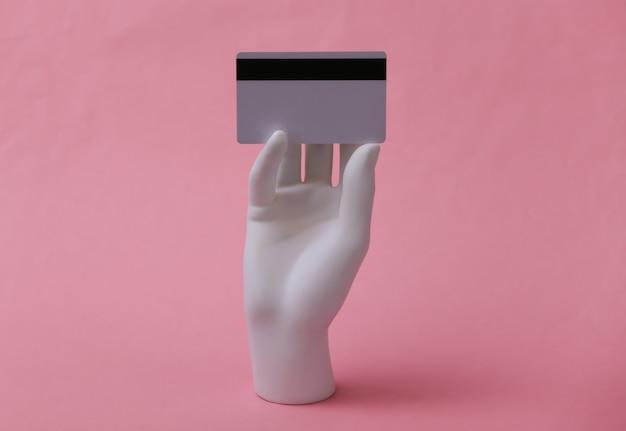 Mão de manequim branco segura um cartão de banco em fundo rosa. compras, crédito, dinheiro online