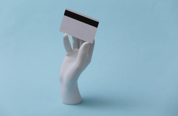 Mão de manequim branco segura um cartão de banco em um fundo azul. compras, crédito, dinheiro online