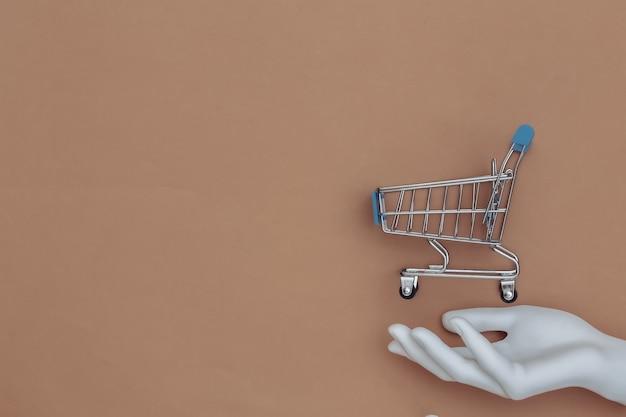 Mão de manequim branco segura um mini carrinho de compras em fundo marrom. vista do topo