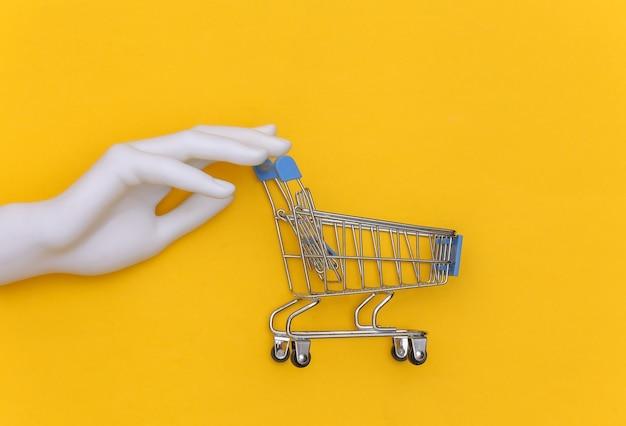 Mão de manequim branco segura um mini carrinho de compras em um fundo amarelo. vista do topo