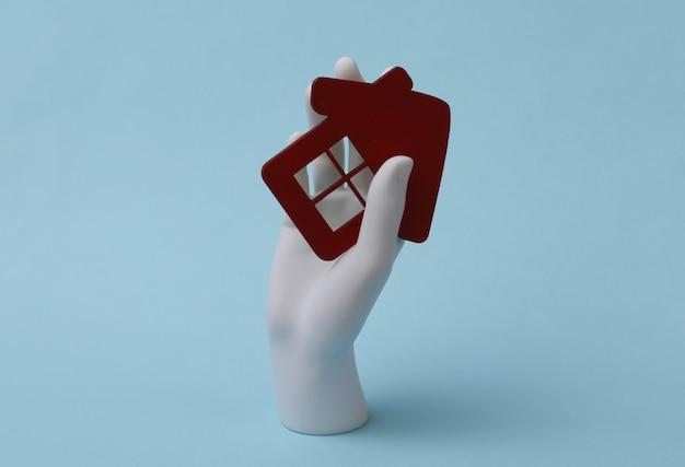 Mão de manequim branco segura uma estatueta de casa sobre fundo azul. comprando propriedade