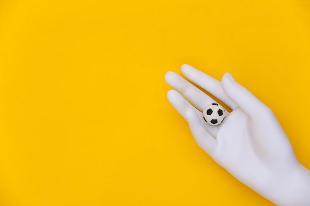 Mão de manequim branco segura uma mini bola de futebol em fundo amarelo.
