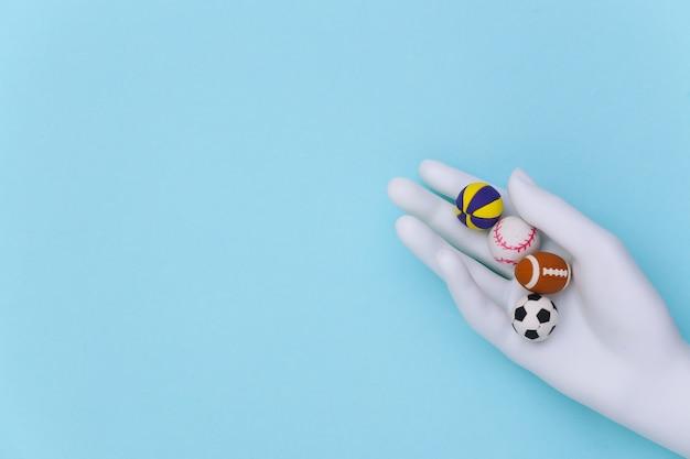 Mão de manequim branco segurando mini bolas de diferentes esportes em um fundo azul. vista do topo