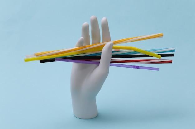 Mão de manequim branco segurando muitos tubos de coquetel de plástico em fundo azul