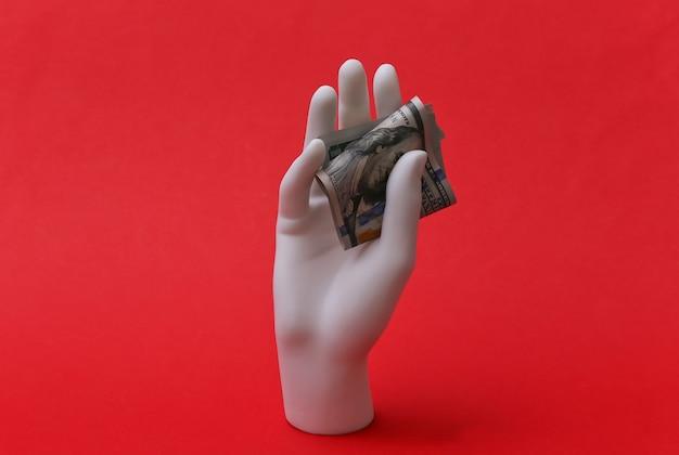 Mão de manequim branco segurando notas de cem dólares em fundo vermelho