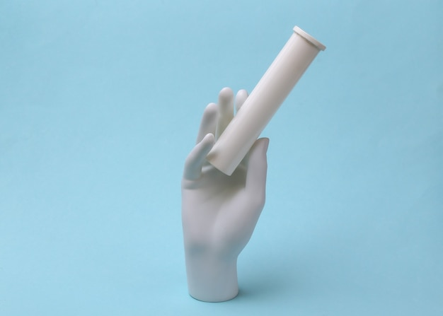 Mão de manequim branco segurando o frasco de comprimidos no fundo azul