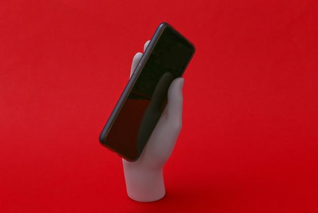 Mão de manequim branco segurando smartphone e fica em fundo vermelho