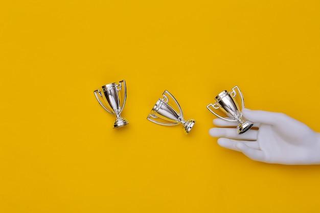 Mão de manequim branco segurando taças do campeonato em fundo amarelo. vista do topo