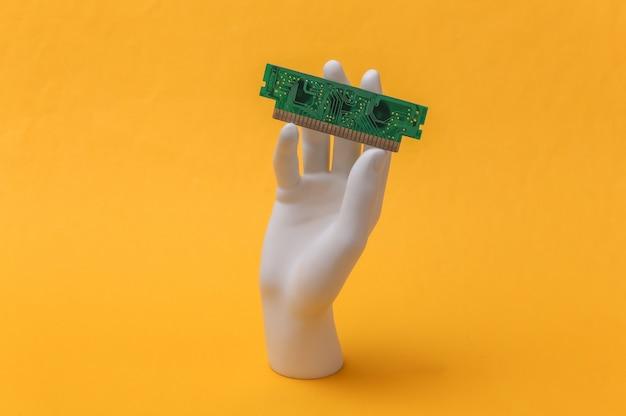 Mão de manequim branco segurando um chip de computador e fica em um fundo amarelo