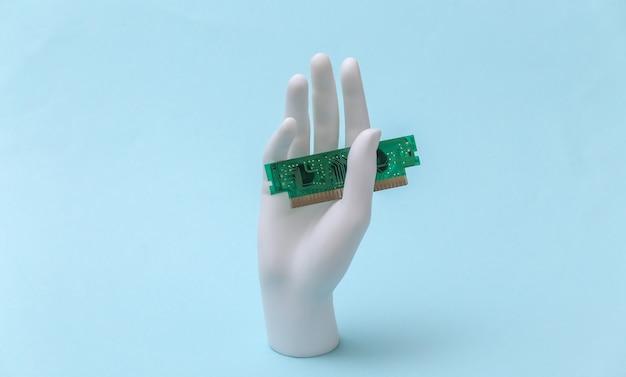 Mão de manequim branco segurando um chip de computador e fica em um fundo azul