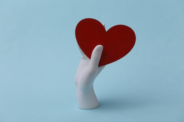 Mão de manequim branco segurando um coração vermelho sobre fundo azul. conceito de dia dos namorados