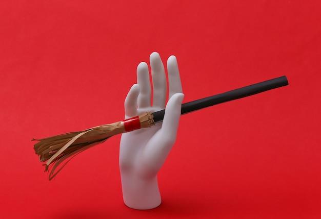 Mão de manequim branco segurando vassoura de bruxa mini sobre fundo vermelho. conceito de halloween