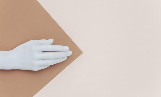 Mão de manequim branco sobre fundo bege marrom. minimalismo. copie o espaço. vista do topo. postura plana